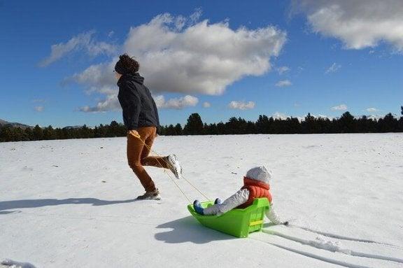 Tata ciągnący dziecko na sankach - zabawy w śniegu