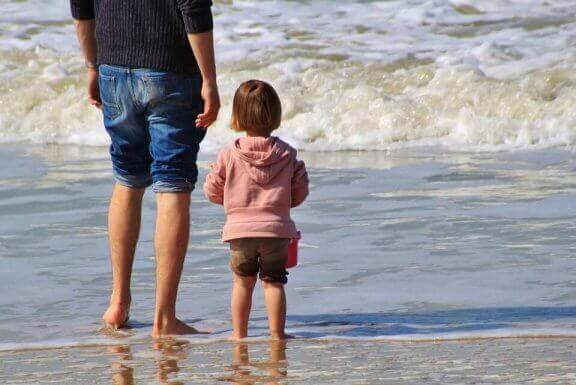 Tata i dziecko stojący na brzegu morza
