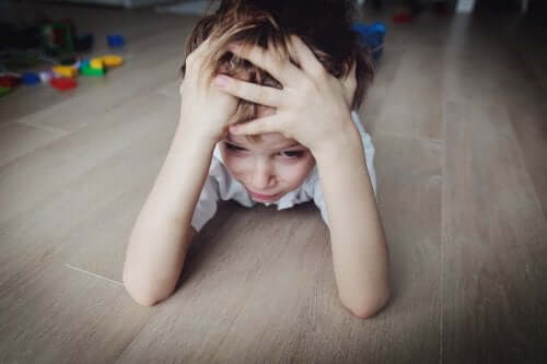 Zestresowany chłopiec leżący na podłodze - jak ochronić dziecko przed stresem