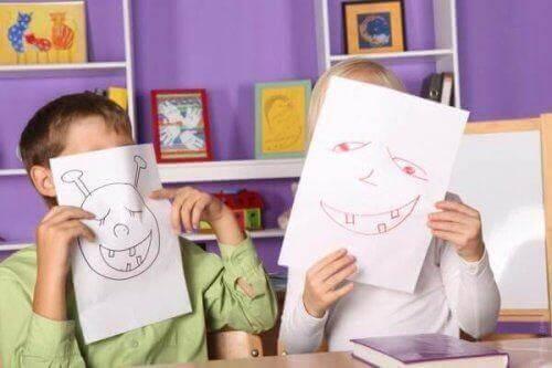 Dzieci zakrywające twarze kartkami z rysunkami