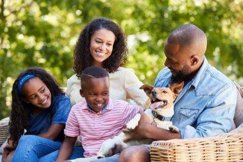 Uśmiechnięci rodzice, dzieci i pies - socjalizacja dziecka