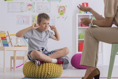 Chłopiec zatykający uszy palcami