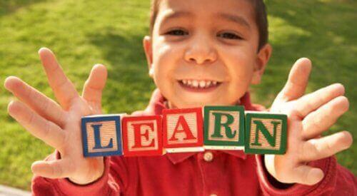 Dziecko trzymające klocki z napisem learn