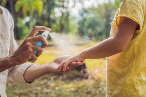 Tata psikający dziecko sprayem przeciwko owadom