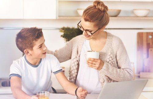 Uśmiechnięta mama klepiąca syna po plecach - nagradzanie dziecka za dobre oceny
