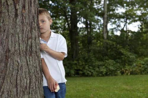 Chłopiec chowa się za drzewem