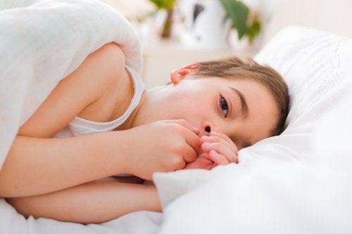 Przeziębiony chłopiec leży w łóżku