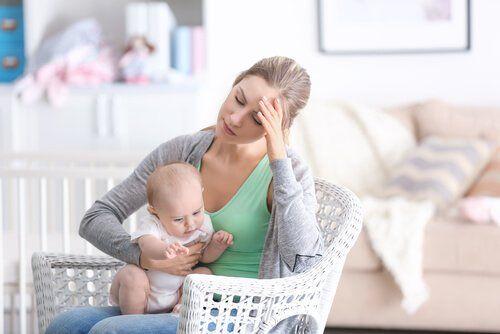 Zmęczona mama trzyma niemowlę - jak zapobiegać depresji poadopcyjnej