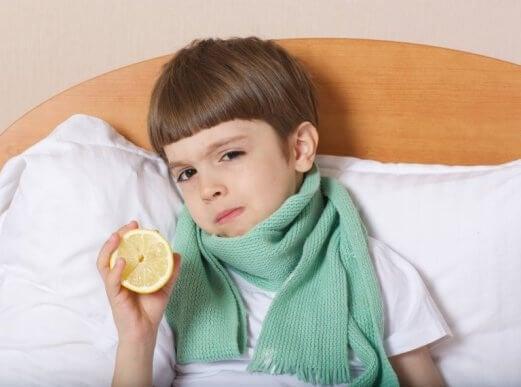Chłopiec w łóżku z szalikiem na gardle