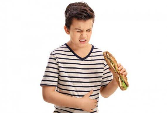 Chłopiec z kanapką w dłoni trzymający się za brzuch