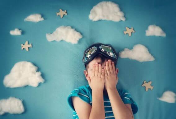 Chłopiec zasłaniający oczy na tle z chmurami