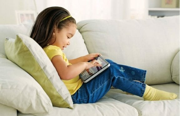 Dziewczynka siedząca na kanapie z tabletem