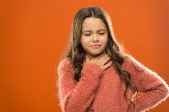 Dziewczynka trzymająca się za gardło - guzki śpiewacze