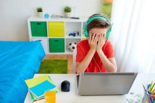 Cyberprzemoc w szkole - chłopiec płacze przed komputerem