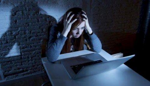 Dziewczyna łapie się za głowę przed komputerem