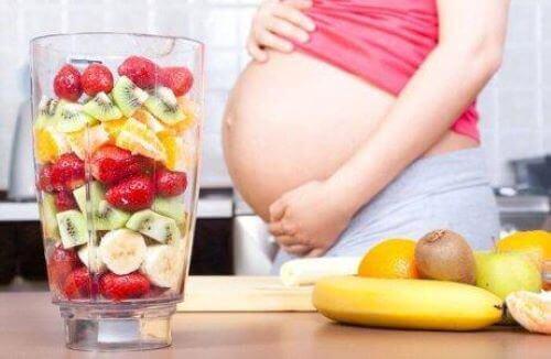 Odżywianie w ciąży - ciężarna kobieta szykuje koktajl owocowy