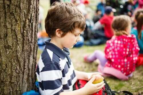 Samotny chłopiec przy drzewie - dziecko ma problem z nawiązywaniem przyjaźni