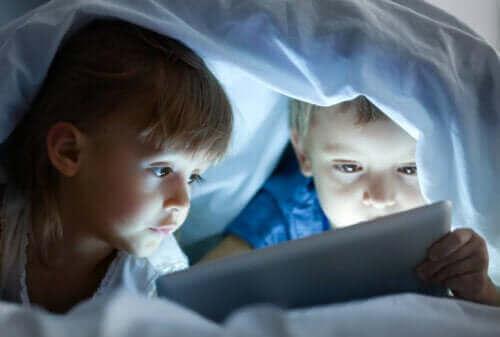 Dzieci używające tabletu pod kocem