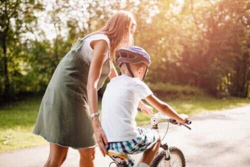 Mama ucząca syna jazdy na rowerze