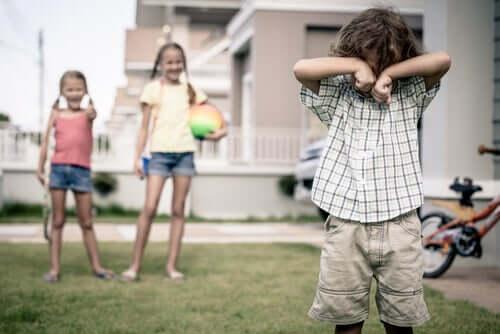 Dzieci wyśmiewające się z chłopca