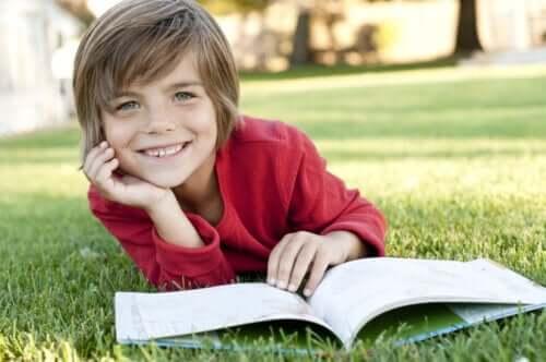 Chłopiec czytający na trawie