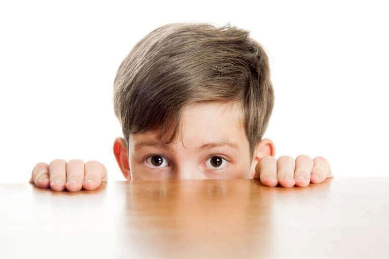 Chłopiec wyglądający zza blatu