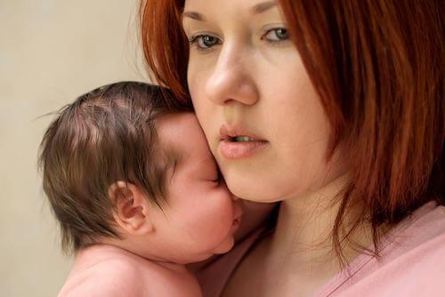 Zmartwiona kobieta z noworodkiem