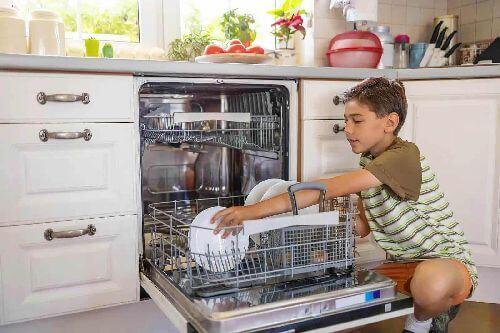 Dziecko wyjmuje naczynia ze zmywarki
